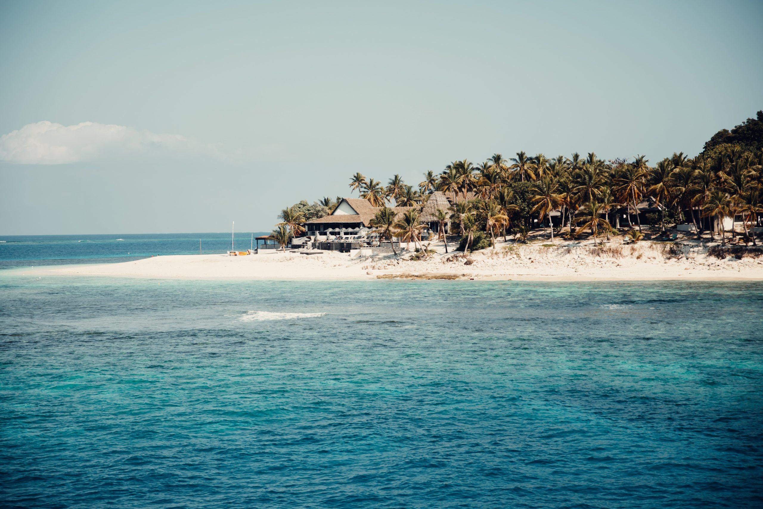 beach hut on an island in fiji overlooking blue ocean water and reef