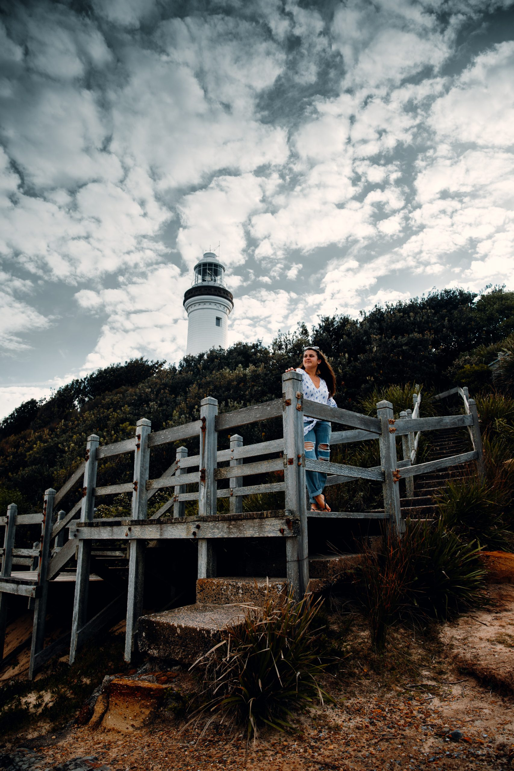 woman standing in front of Norah head lighthouse looking out at the beach and ocean