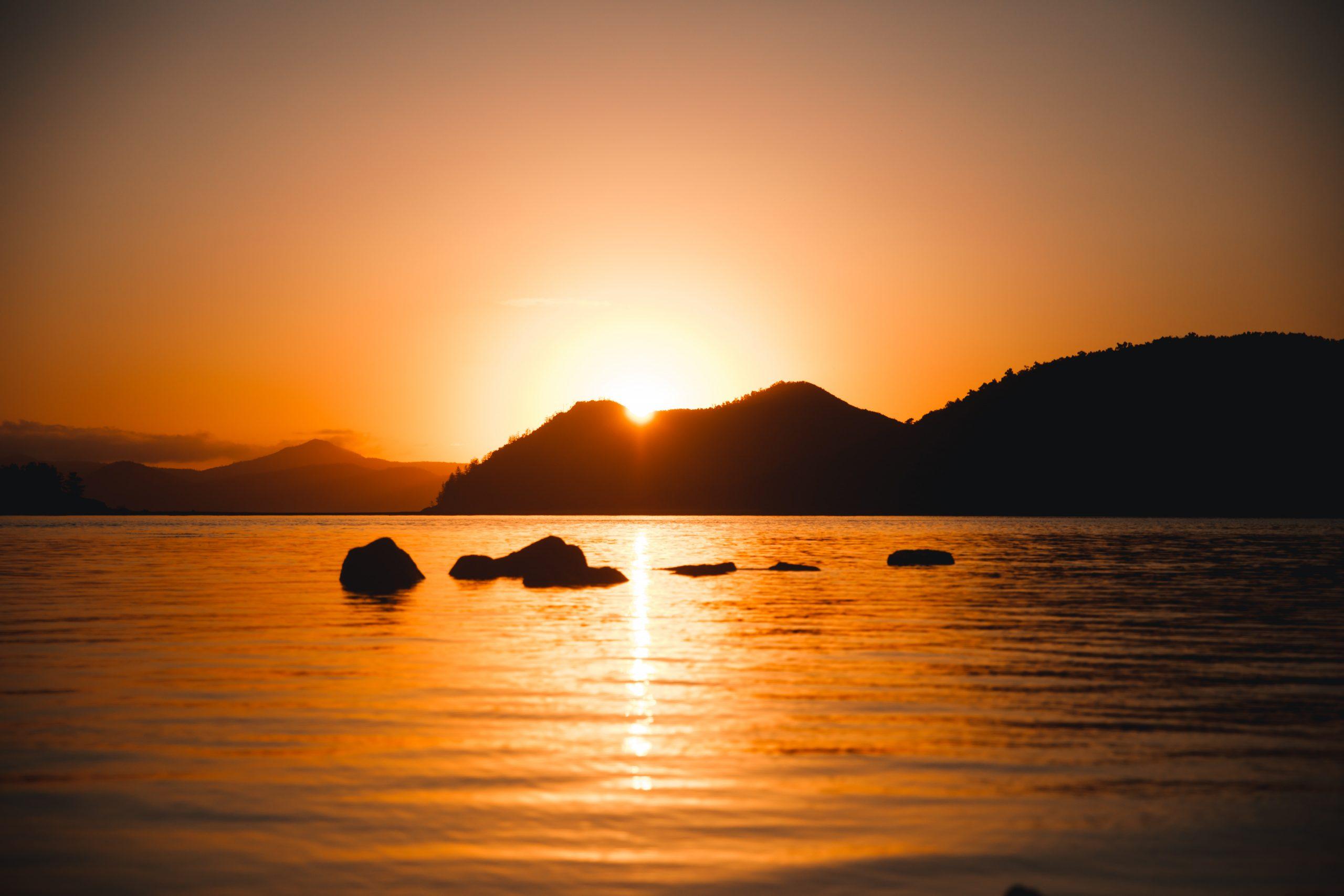 sun peaking through island mountain in the whitsunday islands during incredible sunrise