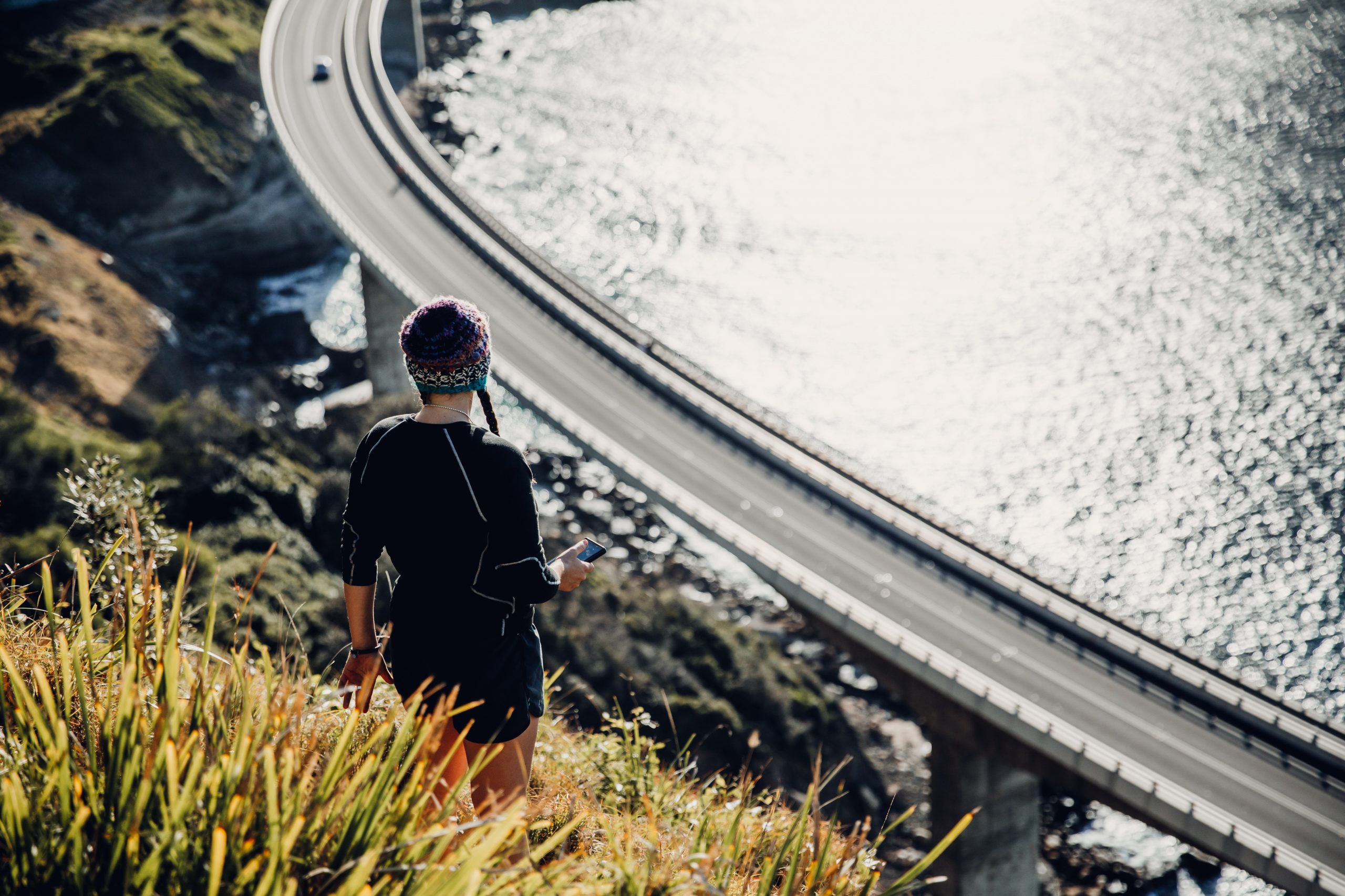 woman looking down at Seacliff bridge at sunrise from a secret hiking trail
